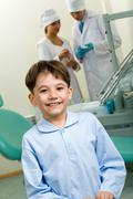 Portrait of happy boy in dentist room on background of two doctors Stock Photos