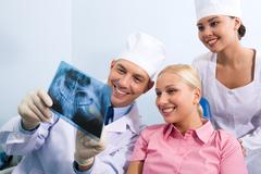 Stock Photo of image of young lady with dentist showing her x-ray photography