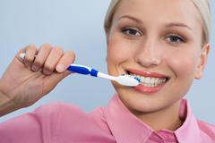 image of happy female holding toothbrush in hand before cleaning teeth - stock photo