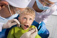 Image of dental examining being given to little boy by dentist and his assistant Stock Photos