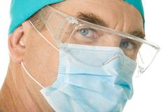 close-up of surgeon wearing mask over white background - stock photo