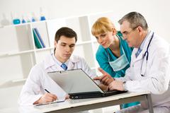 photo of aged physician pointing at laptop display with two colleagues near by l - stock photo