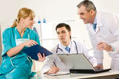 photo of aged physician and young clinician looking at document in nurse's hand - stock photo