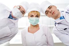 below view of three therapeutists in masks looking at camera - stock photo