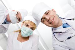 below view of happy doctors with nurse between them looking at camera - stock photo