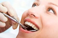 Close-up of patient's open mouth during oral inspection with mirror and hook Stock Photos