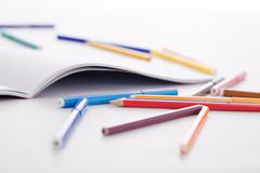 Image of colorful pencils and highlighters with open drawing album near by Stock Photos