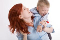 Cute child embracing his beautiful mother and both laughing Stock Photos