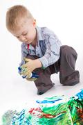 Photo of cute lad holding container with colorful gouache while painting Stock Photos