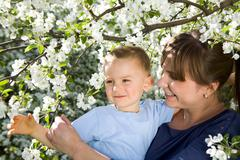 Stock Photo of portrait of happy mother holding her cute son in blooming garden