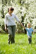 Lovely woman and her son in casual clothes taking a walk down green grass in sum Stock Photos