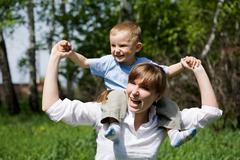 Portrait of joyful woman and playful child on her shoulders having fun outdoors Stock Photos