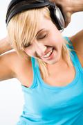 Image of modern teenage girl wearing headphones and keeping her hands on them wh Stock Photos