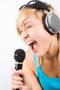 Image of modern teenage girl wearing headphones and singing into microphone Stock Photos