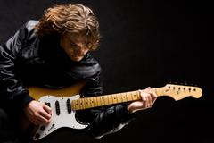 portrait of young modern guitarist playing instrument on black background - stock photo