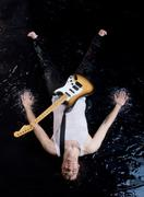 above shot of happy guitarist in vest lying in water and looking at camera - stock photo