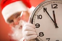 Photo of clock showing five minutes to midnight with santa on background Stock Photos