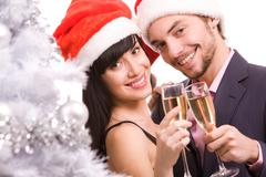 portrait of happy couple with champagne looking at camera and smiling - stock photo