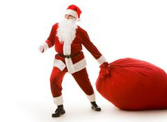 Portrait of happy santa carrying heavy big red sack with presents Stock Photos