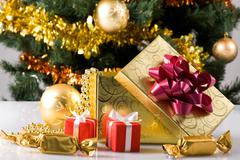 Close-up of giftboxes, sweets and toy ball on background of decorated xmas tree Stock Photos
