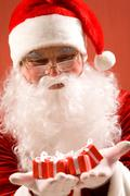 photo of happy santa claus with small giftboxes in hands - stock photo