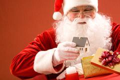 Photo of santa claus putting toy house into small giftbox Stock Photos