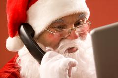 Photo of santa claus calling by phone and smiling Stock Photos