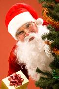 photo of happy santa claus with small giftbox looking at camera out of decorated - stock photo