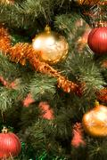 close-up of christmas fir tree decorated with garland and toy balls - stock photo