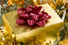 christmas gift surrounded by golden tinsel - stock photo