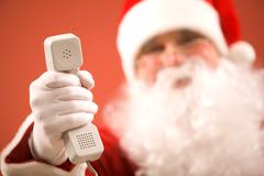 photo of santa claus giving phone receiver to you - stock photo