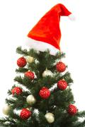 close-up of christmas fir tree decorated with santa cap and toy balls - stock photo