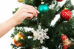 close-up of christmas fir tree being decorated with artificial snowflake - stock photo