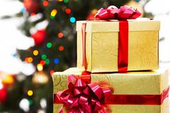 close-up of two giftboxes on background of decorated xmas tree - stock photo