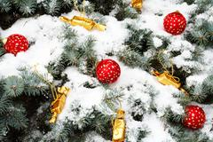 image of red decorative toy balls and sweets in golden wrapping on spruce branch - stock photo