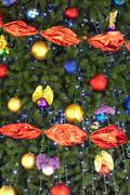 part of christmas fir tree decorated with colorful toy balls and garlands - stock photo