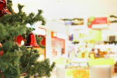 Close-up of red toy bell hanging on green spruce branch Stock Photos