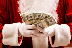 Close-up of santa's hands with stacks of dollar banknotes Stock Photos