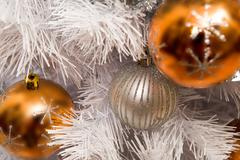 Close-up of toy balls hanging on white fluffy branch of artificial fir tree Stock Photos