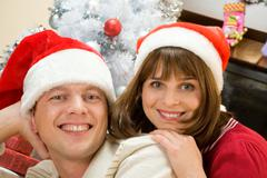 Portrait of happy husband and wife wearing santa caps and looking at camera with Stock Photos