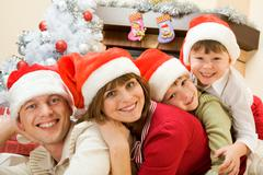 portrait of happy family wearing santa caps and looking at camera with smiles - stock photo