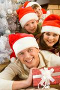Stock Photo of portrait of happy man in santa cap holding giftbox with his family on background