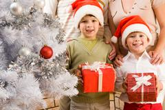 Portrait of happy siblings in santa caps holding giftboxes in hands Stock Photos