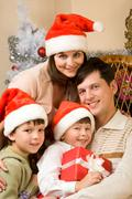 portrait of happy family in santa caps at home - stock photo
