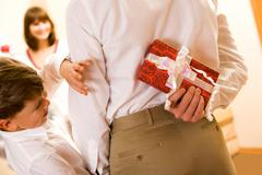 rear view of man holding giftbox in hand with his son near by trying to look it - stock photo