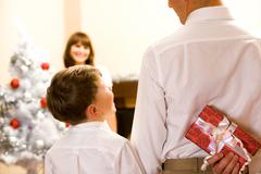 rear view of man holding giftbox in hand with his son near by - stock photo