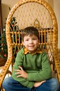 portrait of boy sitting in wicker chair and looking at camera with smile - stock photo