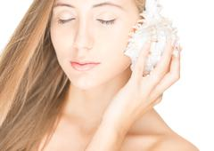 Pretty woman with seashell isolated on white. Stock Photos
