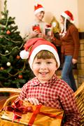 Happy lad with gift in hands looking at camera with smile on christmas day Stock Photos