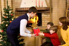 portrait of happy boys receiving cristmas gifts from their parents at home - stock photo